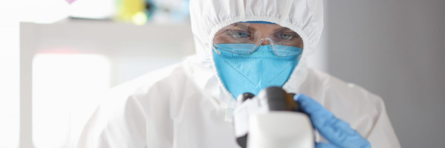 doctor-in-protective-medical-suit-mask-and-glasses-looks-through-microscope-medical-research-min